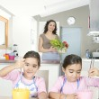 Young twin daughters beating eggs in the kitchen with mum. — Stock Photo