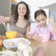 Mum and young daughter beating eggs in a home kitchen. — Stock Photo