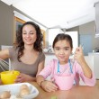Mother and daughter beating eggs in the kitchen at home while sitting together at a wooden table. — Stock Photo #19823089