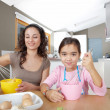 Mother and daughter beating eggs in the kitchen at home while sitting together at a wooden table. — Stock Photo