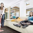 Stockfoto: Young mum using vacum cleaner wthile her two twin daughters look at book in living room.