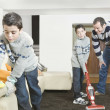 Dad and twin sons cleaning their home's living room. — Stock Photo