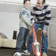 Foto Stock: Dad and boy using a vacum cleaner at home.