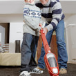 Dad and son vaccum cleaning their living room, smiling and bonding. - Stock Photo