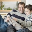 Dad and son reading a magazine while lounging on the living room's sofa. — ストック写真