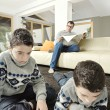 Stock Photo: Dan and twin sons reading in their home's living room.