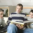 Dad and identical twin sons reading a book at home together. — Stock Photo