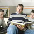 Dad and identical twin sons reading a book at home together. — Stock Photo #19823235