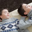 Two identical twin brothers sleeping on a white leather couch wihle wearing identical jumpers. — Stockfoto