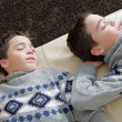 Stock Photo: Two identical twin brothers sleeping on white leather couch wihle wearing identical jumpers.