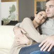 Couple relaxing on sofa at home, holding each other. — Stock Photo