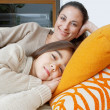 Mother and daughter resting on a white leather sofa at home, smiling. — Stock Photo