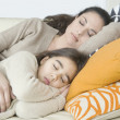 Young mum and daughter sleeping on a sofa at home. — Stockfoto