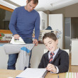 Father and son doing homework and ironing clothes while in the kitchen at home. — Stock fotografie
