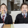 ストック写真: Two identical twin brothers playing with pencils while doing their homework at home on kitchen table.