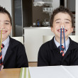 Stock Photo: Two identical twin brothers playing funny games while doing their homework at home on the kitchen table.