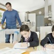 Two twin brothers doing homework on kitchen table while dad irons clothes. - Stock Photo