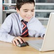 Young boy using a laptop computer at home to do his homework at home, smiling. — Stock Photo #19823835