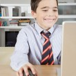 Young boy using a laptop computer at home to do his homework, smiling. — Stock Photo #19823837