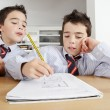 Stock Photo: Two young twin brothers doing homework at home, sharing wood table.