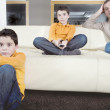 Father and identical twin sons watching tv in the living room at home. — Stock Photo
