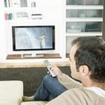 professionell man använder en TV-fjärrkontroll för att byta kanal på TV hemma — Stockfoto