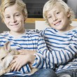Two twin brothers stroking their pet rabbit on a sofa at home. - Стоковая фотография