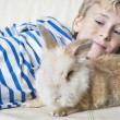 Young boy stroking his pet rabbit at home. - Photo