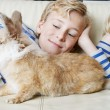 Stock Photo: Two brothers and their rabbit pet lay together on a sofa at home, smiling.