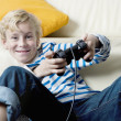 Stock Photo: Young boy playing with playstation at home.