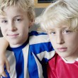 Portrait of two kids wearing soccer uniforms of different teams. - Stock Photo