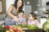 Young mum chopping vegetables with twin daughters in a family home kitchen. — Stockfoto