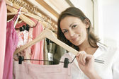 Close up of a store assistant sorting clothes on store's rails, smiling. — Stock Photo
