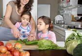 Mum and twin daughters learning to chop vegetables together in the kitchen, using a chopping board and surrounded by fruit and vegetables. — Stock Photo