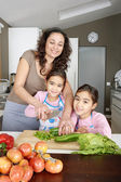 Young family kids learning to chop vegetables in the kitchen with mum, smiling. — Fotografia Stock