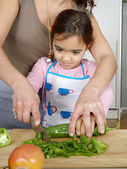 Mother teaching daughter to chop vegetables together in the kitchen using a chopping board and smiling. — Stock Photo