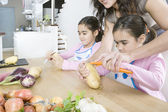 Young mum teaching twin daughters how to peel potatoes. — Stock Photo
