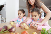 Mother teaching twin daughters to peel potatoes in the kitchen using a chopping board and peelers. — Stock Photo