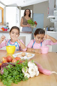 Two identical twin sisters beating eggs in their home kitchen — Stock Photo