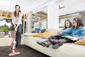 Jovem mãe usando um wthile de vacum cleaner suas filhas dois gêmeas olhem para um livro na sala de estar. — Foto Stock