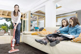Young mum using a vacum cleaner wthile her two twin daughters look at a book in the living room. — Foto Stock