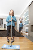 Mother and daughters cleaning the house together, smiling. — Stock Photo