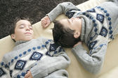 Two identical twin brothers sleeping on a sofa in the living room. — Stock Photo