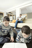 Dan and twin sons reading in their home's living room. — Stock Photo