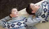 Two identical twin brothers sleeping on a white leather couch wihle wearing identical jumpers. — Stock Photo