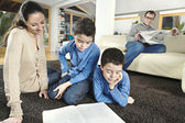 Family of four reading in their home's living room. — Stock Photo