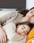 Mother and daughter sleeping on a white leather sofa at home. — Stock Photo