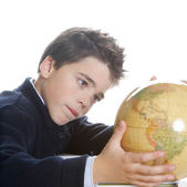 Young boy using a world .globe to learn geography while doing his homework near a window — Stock Photo