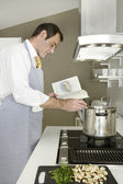 Businessman using a recepe book to cook at home. — Stock Photo