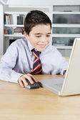 Young boy using a laptop computer at home to do his homework at home, smiling. — Stock Photo